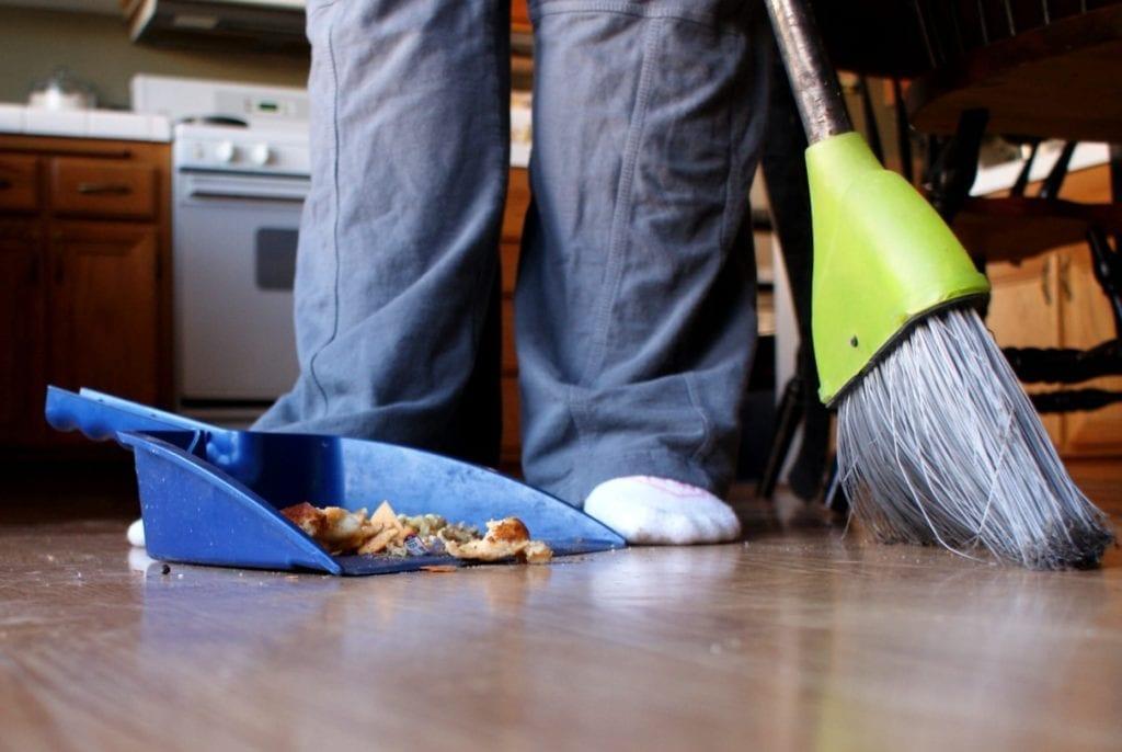 Broom, dustpan, and child's feet