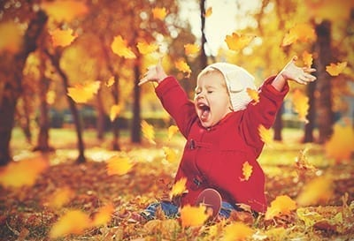 Child playing in leaves - AdobeStock_70782096 400px