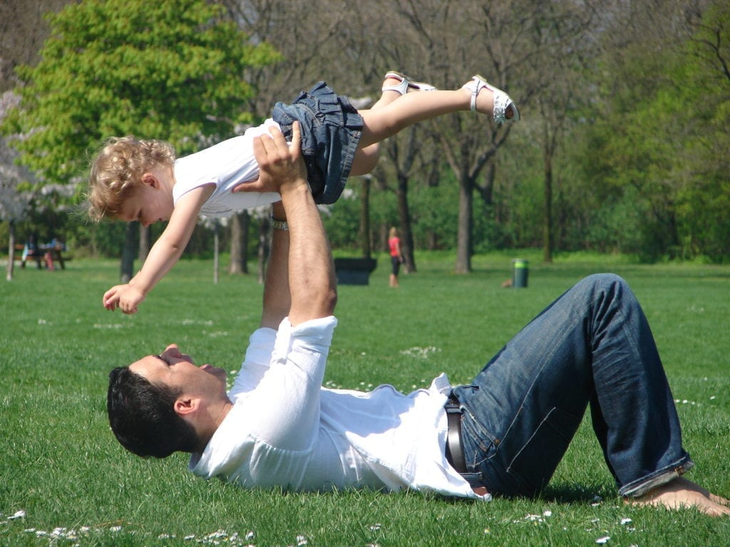 Dad playing airplane with daughter