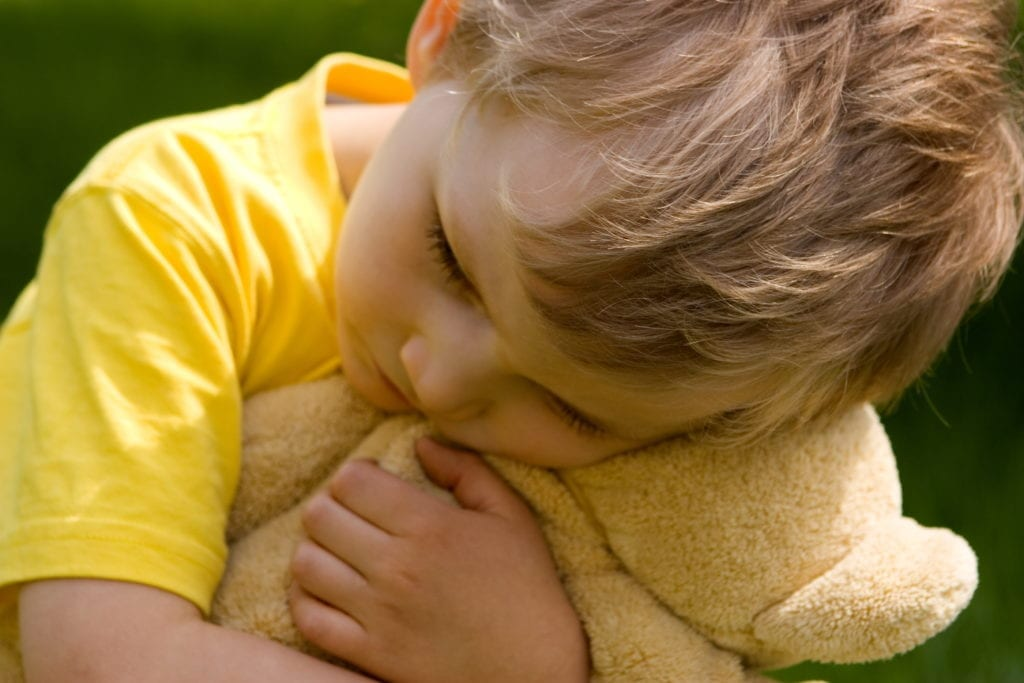 child hugging bear