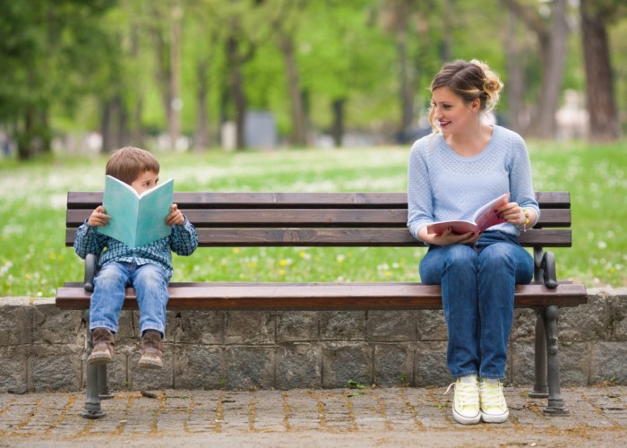 woman and little boy reading at opposite ends of a park bench