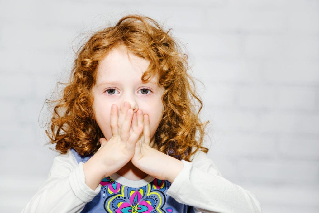 Little girl with hands over mouth